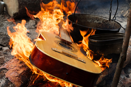 Guitar in flame and old sooty cauldrons on campfire at forest