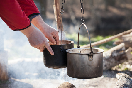 Man cooking in sooty old pots on bonfire at sunny summer day