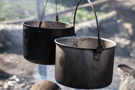 Cooking in two sooty old cauldrons on campfire at sunny day. Close-up view. Stock fotó