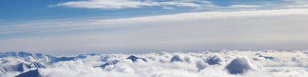 Panoramic airplane view of snowy mountains covered with beautiful sunlight clouds at sunny winter day. Caucasus Mountains, Georgia, region Gudauri.