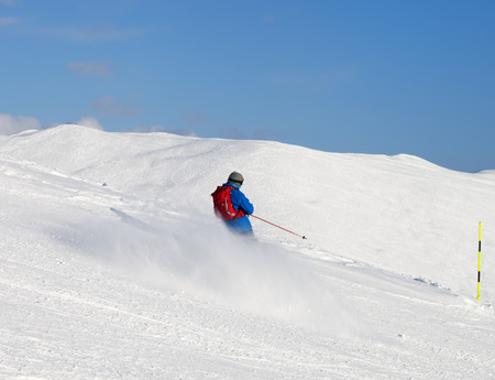 Skier downhill on snowy ski slope in sunny winter day. Caucasus Mountains, Georgia, region Gudauri.