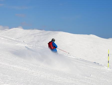 Skifahrer bergab auf verschneiter Skipiste am sonnigen Wintertag. Kaukasus, Georgien, Region Gudauri.
