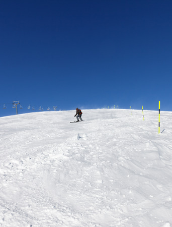 Skier downhill on snowy ski slope in sunny winter day. Caucasus Mountains, Georgia, region Gudauri. Wide angle view.