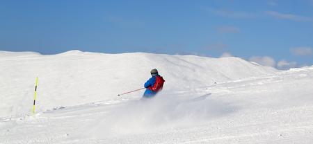 Panoramic view on skier downhill on snowy ski slope in sun winter day. Caucasus Mountains, Georgia, region Gudauri.