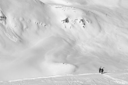 Two skiers with skis on his shoulder and off-piste slope with traces of skis, snowboards and avalanches. Caucasus Mountains in sun cold winter day, Georgia, region Gudauri. Black and white toned landscape.