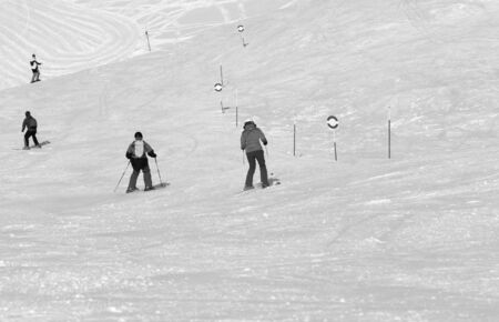 Skiers and snowboarders downhill on snowy ski trace at sunny day. Caucasus Mountains in winter, Georgia, region Gudauri. Black and white toned landscape.