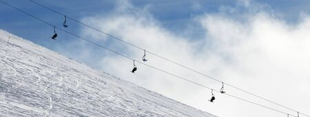 Panoramic view on snow off-piste ski slope and chair-lift in fog. Caucasus Mountains in winter, Georgia, region Gudauri.