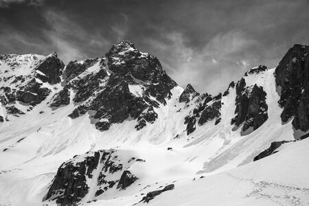 Snowy sunlit rocks with traces from avalanches and storm clouds on sky at windy winter day. Turkey, Kachkar Mountains, highest part of Pontic Mountains. Black and white toned landscape.
