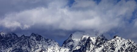 High snowy mountains in clouds at sunny winter day. Caucasus Mountains. Georgia, region Svaneti. Panoramic view. 版權商用圖片