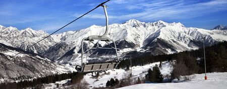Ski slope and chair-lift in snowy winter mountains at sun windy day. Caucasus Mountains. Hatsvali, Svaneti region of Georgia. Panoramic view.