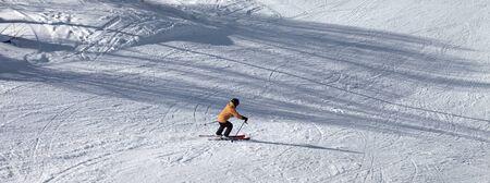 Skier descents on snowy ski slope at sun winter day. Caucasus Mountains. Hatsvali, Svaneti region of Georgia. Panoramic view.