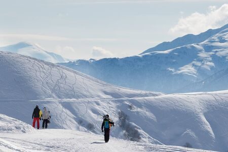 Skiers and snowboarders go on snowy road at sunny winter morning. Caucasus Mountains, Georgia, region Gudauri.