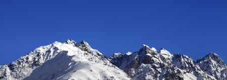 Snowy rocks and blue clear sky at nice winter day. Caucasus Mountains. Svaneti region of Georgia. Panoramic view.