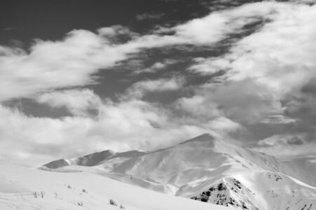 Black and white snowy ski slope and sky with clouds in winter evening. Tetnuldi, Caucasus Mountains, Svaneti region of Georgia.