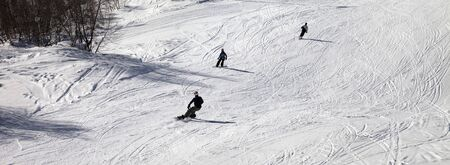 Skiers and snowboarders on snowy ski slope at sun winter day. Panoramic view.