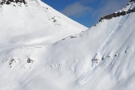 Snowy off-piste slope with traces of skis, snowboards and avalanches. Caucasus Mountains in sunny winter day, Georgia, region Gudauri. 版權商用圖片