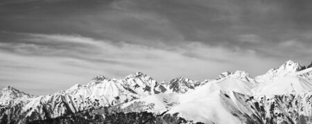 Sunlight snowy mountains and sky with clouds in sunny day. Caucasus Mountains at winter. Georgia, region Svanetia. Black and white retro toned landscape.   版權商用圖片