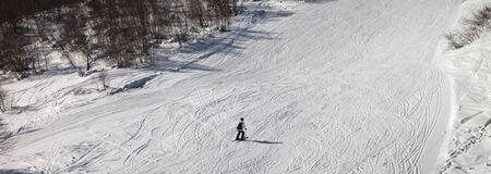 Skier downhill on snowy ski slope at sun winter day. Panoramic view. 版權商用圖片