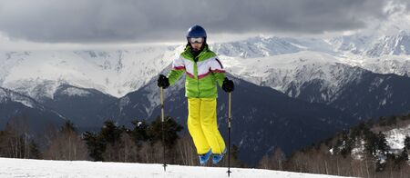 Young skier jump with ski poles in sun mountains and cloudy gray sky. Caucasus Mountains. Hatsvali, Svaneti region of Georgia. Panoramic view.