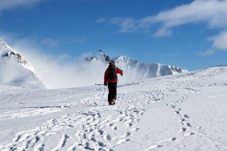 Skier with skis on his shoulder go up to top of snowy mountain in nice sun day. Caucasus Mountains in winter, Georgia, region Gudauri, Mount Kudebi. 版權商用圖片