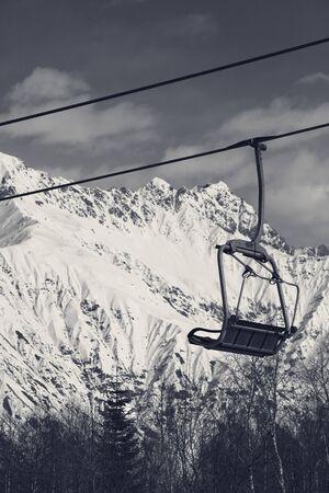 Ski-lift on ski resort and snowy mountains at sunny winter day. Caucasus Mountains. Hatsvali, Svaneti region of Georgia. Black and white retro toned landscape.