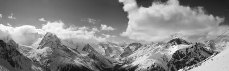 Black and white panorama of snowy sunlit mountains in clouds sunny winter evening. Caucasus Mountains, region Dombay.