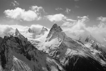 Winter snowy sunlit mountains in clouds. Caucasus Mountains, region Dombay, Mount Beelalakaya. Black and white toned landscape. 版權商用圖片