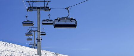 Panoramic view on ski-lift, snowy off-piste slope and blue clear sky in sun cold day. Caucasus Mountains at winter. Mount Tetnuldi, Svaneti region of Georgia. 版權商用圖片