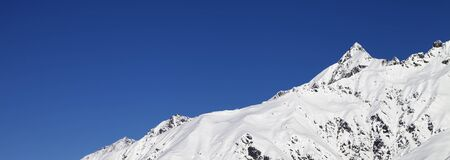 Snowy mountain peaks and blue clear sky. Caucasus Mountains at winter. Georgia, region Svaneti. Panoramic view.