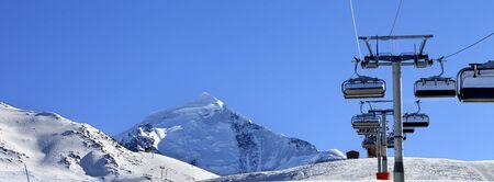Ski-lift at ski resort in sun cold morning. Snowy Caucasus Mountains at winter. Mount Tetnuldi, Svaneti region of Georgia. Panoramic view.