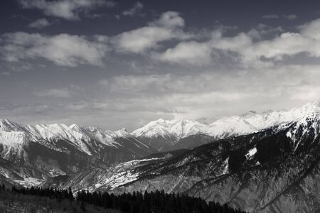 Snowy mountains and sky with clouds at winter sun day. Caucasus Mountains. Georgia, region Svaneti. Black and white retro toned landscape.