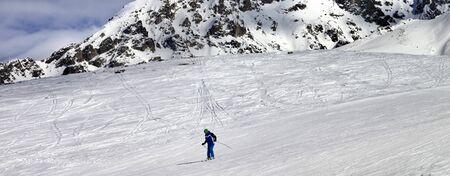 Skier on snowy ski slope at sun winter day. Caucasus Mountains. Tetnuldi, Caucasus Mountains, Svaneti region of Georgia. Panoramic view.
