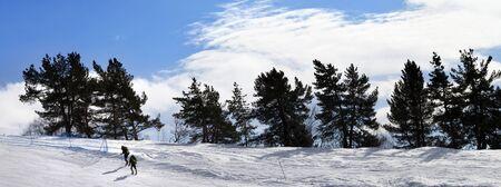 Two hikers on snowy slope in sun winter day. Caucasus Mountains, Tetnuldi, Svaneti region of Georgia. Panoramic view.