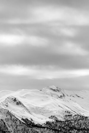 Snowy mountains and gray cloudy sky at winter. Caucasus Mountains. Svaneti region of Georgia. Black and white toned landscape.