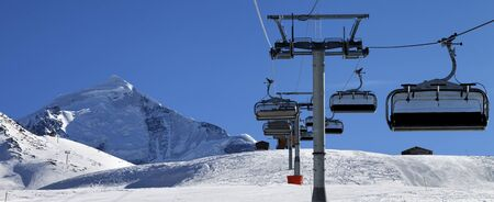 Panoramic view on chair lift in snowy mountains at nice sunny day. Caucasus Mountains at winter. Mount Tetnuldi, Svaneti region of Georgia.