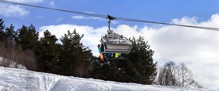 Skiers and snowboarders on chair-lift in winter mountain. Caucasus Mountains. Mount Tetnuldi, Svaneti region of Georgia. Panoramic view. 版權商用圖片