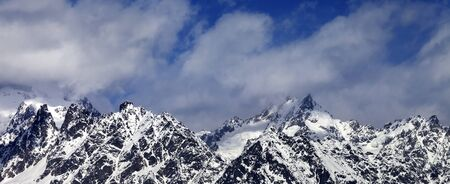Panoramic view on snowy rocks and blue sky with clouds at sunny winter day. Caucasus Mountains. Georgia, region Svaneti. Foto de archivo