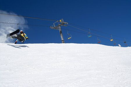 Snowboarder fall down with snow splashes on snowy ski slope and chair lift at background. Caucasus Mountains in sunny winter day, region Dombay.