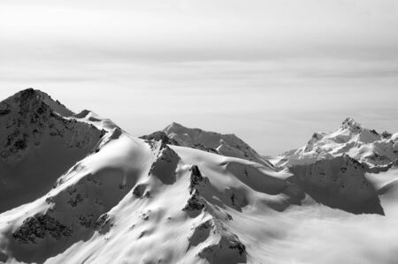 Black and white snowy sunlit mountains. View from ski slope on Mount Elbrus at sun winter evening. Caucasus Mountains.