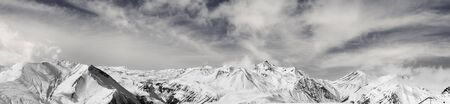 Larger panorama of winter snowy mountains and sky with sunlit clouds. Stock fotó