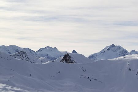 Snowy slope at high winter mountains and sunlit cloudy sky. Italian Alps. Livigno, region of Lombardy, Italy.