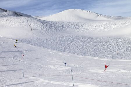 Trace for ski slalom with gates marked by flags, prepared by snowcat and off-piste slope in snowy high mountains at sunny winter day. Italian Alps. Livigno, region of Lombardy, Italy, Europe. 写真素材