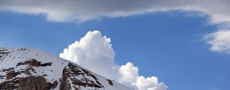 Panoramic view on snowy rocks and blue sky with sunlit clouds at sunny winter day
