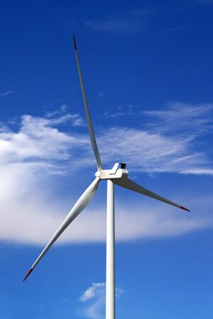 Wind turbine and blue sky with clouds at windy day. Close-up view.