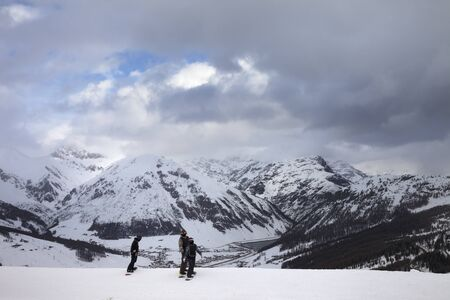 Group of snowboarders starts on off-piste descent. High snowy mountains and cloudy storm sky at winter before blizzard. Ski area Mottolino Fun Mountain, Italian Alps. Livigno, Lombardy, Italy, Europe. Standard-Bild