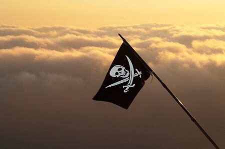 Jolly Roger (pirate flag) on wind and sea in sunset cloudy sky at background 版權商用圖片