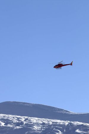 Helicopter in blue clear sky and snowy ski slope in high mountains at sunny winter evening