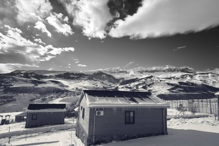 Small wooden houses at snowy winter mountains and sky with clouds. Caucasus Mountains, Shahdagh, Azerbaijan. Wide angle view. Black and white toned image.