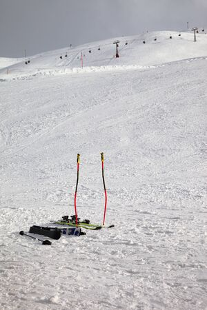 Skiing equipment: ski poles, skis on snowy slope, chair lift and gray cloudy sky at background. Ski area Mottolino Fun Mountain, Italian Alps in winter evening. Livigno, Lombardy, Italy, Europe. Banque d'images - 140634048