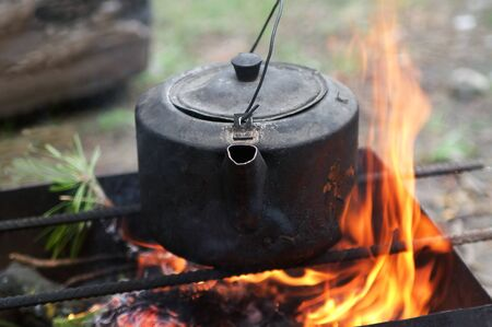Sooty old teakettle on bonfire with smoke at forest in sunny summer day. Selective focus.